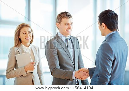 Satisfied business partners shaking hands, personal assistant standing by one of them