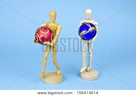 Two wooden artist manikin with christmas baubles on blue azure background