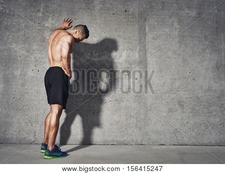Young man resting after an active fitness training while standing against gray wall with copy space area for your text message satisfied fit male man resting after an active fitness training