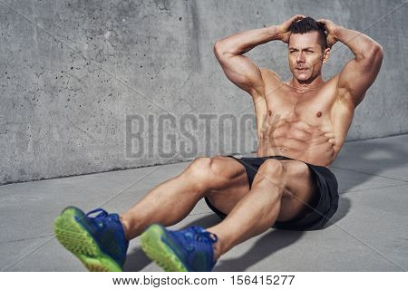 Male fitness model doing sit ups and crunches exercising abdominal muscles six pack visible wearing no shirt
