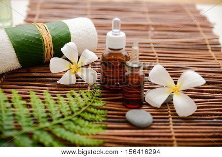 frangipani with massage oil and massage ball ,stones,fern on mat