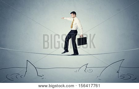 A brave businessman walking on tightrope expanded aboved rawn ocean with shark fin concept poster