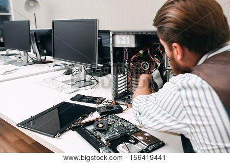 Broken computer disassembling, close-up. Repairman take apart CPU to find failure reason. Electronic repair, renovation concept