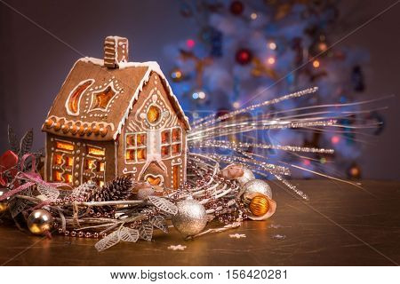 Gingerbread house in Christmas wreath. Gingerbread house with lights inside.