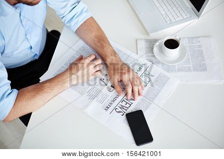 Morning newspaper, cup of black coffee and laptop on office worker s desk