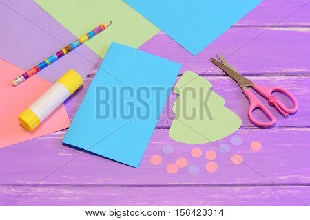 How to make Christmas card from colored paper. Step. Colored paper set, scissors, pencil, Christmas tree template, glue stick, Christmas tree and balls cut from paper. Creative crafts ideas for kids