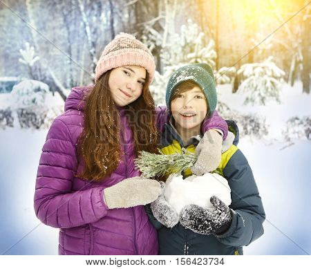 teen siblings boy and girl brother and sister in winter warm clothes mittens close up portrait on the snow park background. Kids walking on winter
