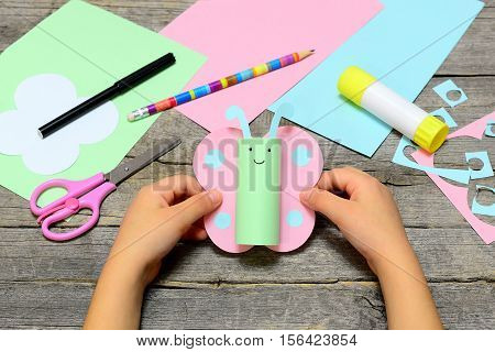 Child holding colored paper butterfly in hands. Child shows a fun paper diy. Stationery on an old wooden background. Preschool paper and glue crafts activities. Children creative abilities development