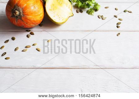 White wooden background with pumpkin frame. Squash with seeds on wood, free space for text or advertisement. Seasonal design, autumn creativity, fall backdrop