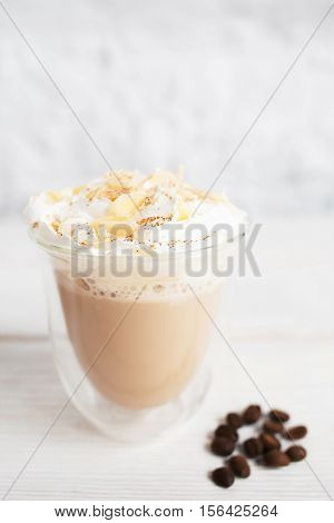 Close-up of cappuccino cup with coffee beans on white background. Tasty appetizing creamy latte in glass mug. Dessert, restaurant serving, hot beverage concept