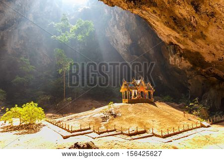 Morning sunbeam on golden buddhist pavilion in wild cave Sam Roi Yot Thailand poster