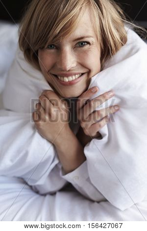 Young blond woman snuggled up in duvet portrait