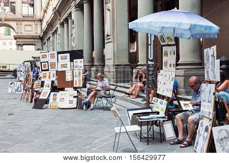 FLORENCE ITALY - JULY 13 2016: Painters working and selling artwork in Florence near Uffizi gallery Italy