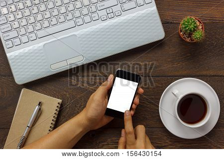 Top view business man using mobile phone and coffee laptop note book cactus on wooden office desk.