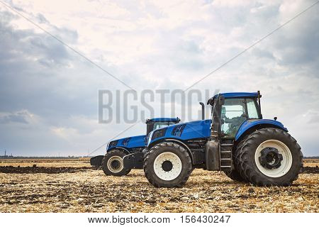 two modern tractors, agricultural machines, cultivation of the soil on the farm, a tractor working in a field, agricultural machinery in the work
