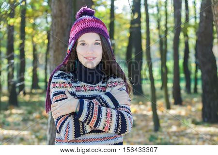Freezing young woman is wearing knitted woolly hat and embracing herself
