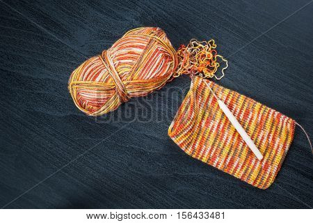 Skein of thread and a crochet hook with case on black background.