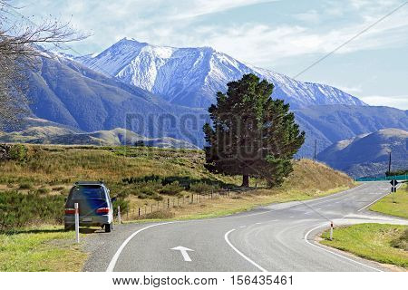Long winding road stretching out into the distance with snow mountain background in New Zealand