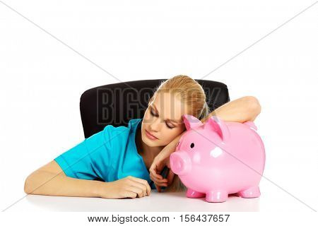 Young tired female doctor or nurse sitting behind the desk and holding a piggybank