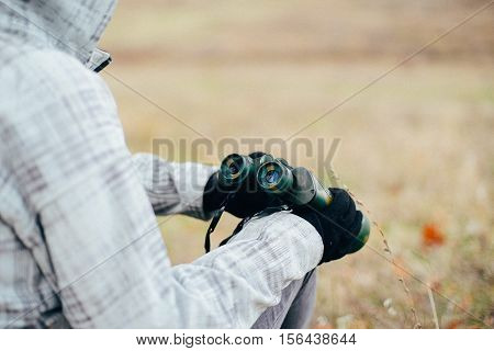 Young woman looking through binoculars on a autumn nature. Binocular, traveler, hiking.  young caucasian female hiker holding in his hand binoculars. Horizontal shape, front view,