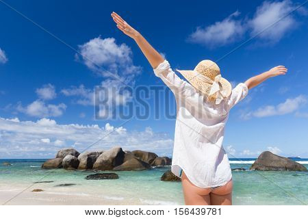 Woman arms rised, wearing white loose tunic over bikini and beach hat, enjoying amazing sea view on Mahe Island, Seychelles. Summer vacations on picture perfect tropical beach concept.