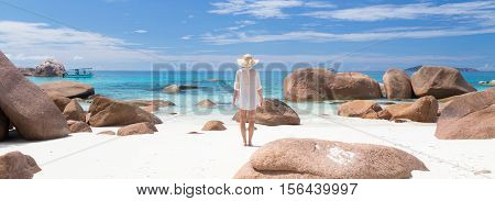 Woman wearing white loose tunic over bikini and beach hat on Anse Lazio beach on Praslin Island, Seychelles. Summer vacations on picture perfect tropical beach concept.