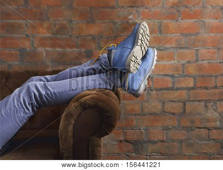 Half body of a female posing her jeans and boots on a sofa
