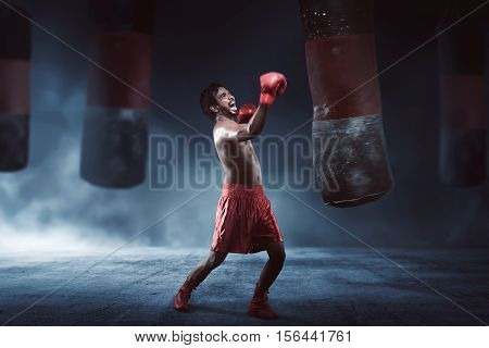 Asian Male Boxer Practicing With A Punching Bag