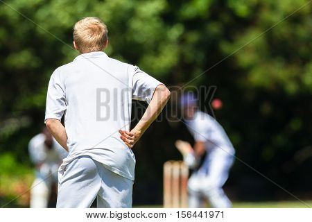 Cricket teenagers schools game fielder batsman bat ball action photo.