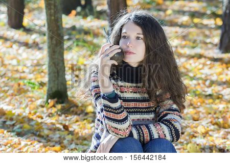 Woman is wearing knitted snowflakes pattern wool sweater and holding hot yerba mate calabash gourd