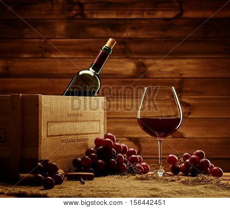 Bottle, glass and red grape on a wooden table.