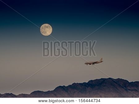 Super moon and landing airplane, desert of the Negev, Israel