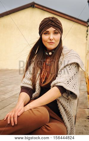 Smiling hipster brunette woman sitting, smiling and looking at camera, fashion autumn outfit, hat and cardigan, long hairs, urban style outfit