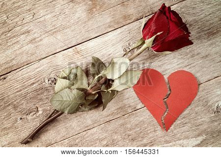 Divorce concept - red broken heart with old rose on wooden background