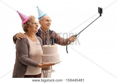 Happy seniors with party hats and a birthday cake taking a selfie with a stick isolated on white background