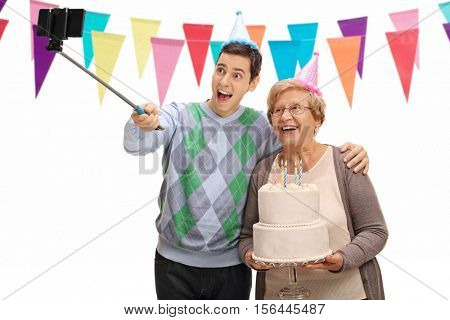Young man and a mature woman with party hats and a birthday cake taking a selfie with a stick isolated on white background