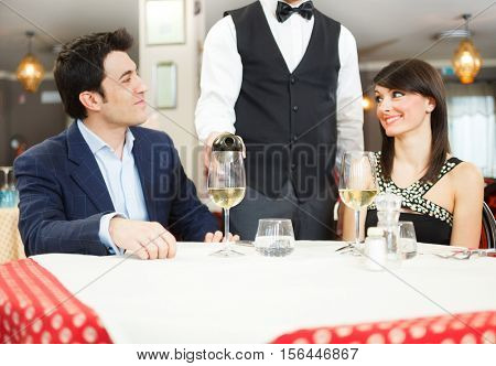 Waiter pouring wine to a couple in a restaurant