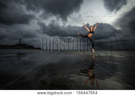 Woman practicing dance and reflected in the water