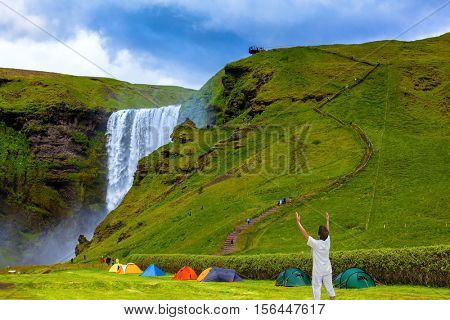 Grand waterfall Skogafoss. Near a waterfall put some colorful tourist tents. Elderly woman shocked by the beauty of the waterfall