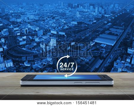 24 hours service icon on modern smart phone screen on wooden table over city tower street and expressway Full time service concept