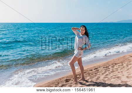 beautiful brunet woman walking on a beach in white dress