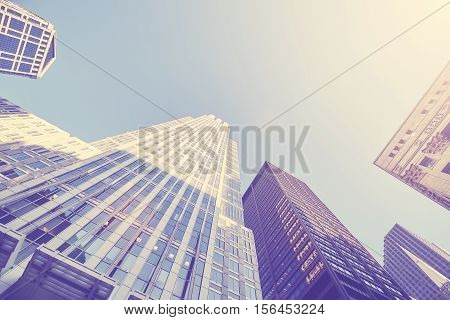 Retro stylized photo of skyscrapers in Chicago at sunset looking up perspective USA.