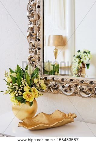 Golden vintage vase with flowers near beautiful antique mirror