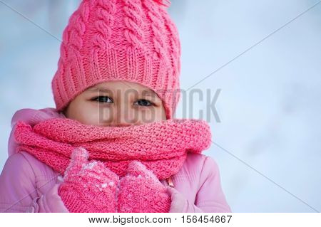 H child girl portrait in knitted warm woolen clothes scarf Kids fashion concept.Xmas poster.Winter holiday wallpaper.