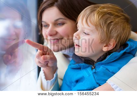 Happy young mother and little toddler boy looking out through window of a train, while it moving. Family, woman and funny cute kid son traveling together and making winter vacation. Travel concept.