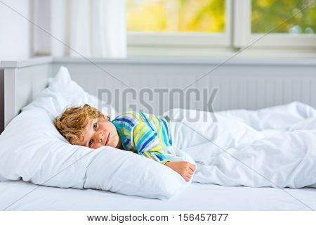 Adorable happy little kid boy after sleeping in his white bed in colorful nightwear near big window with green and yellow autumn foliage. Funny happy child playing and smiling. Family, vacation, childhood concept
