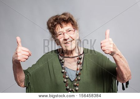 Stylish seniors 90 years old woman. Studio shot. Granny female showing ok