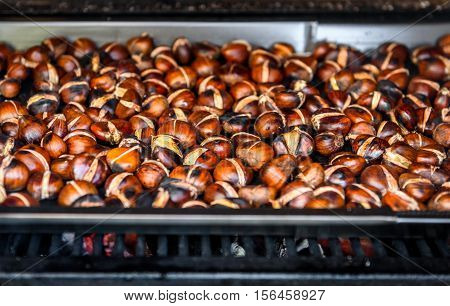 Roasting Grilled Chestnuts On Barbecue With Flames, Fire And Charcoal.
