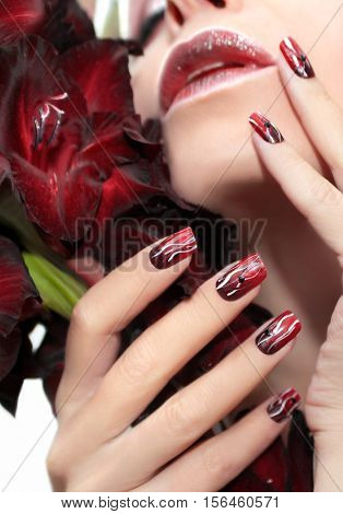 Red manicure with white wavy lines and black rhinestones on a female hand.