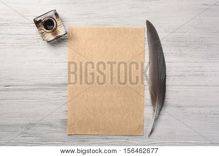 Inkwell with feather and sheet of paper on white wooden background